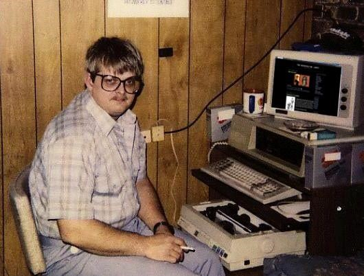 Computer hacker sitting by old computer